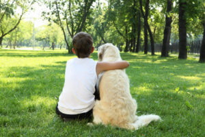 Boy and Dog Sitting in Grass from Back