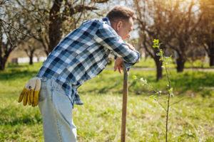 Mature gardener leaning on shovel in backyard